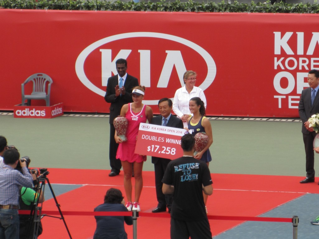 Doubles champions Irina-Camelia Begu and Lara Arruabarrena with the Kia representative