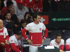 A concerned Federer looked on at start of match before leaving to prepare for his match