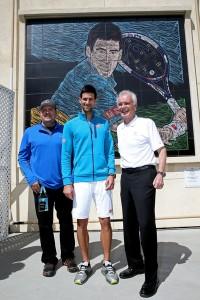 Artist Mike Sullivan and tournament CEO Raymond Moore pose with tennis player, Novak Djokovic during the BNP Paribas Open
